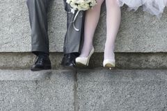 Bride and groom. Sitting on a stone parapet Royalty Free Stock Photos