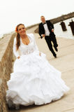 Bride and groom. Groom running after the bride on a peer by the sea Royalty Free Stock Photo
