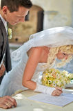 Bride and Groom. At their wedding day signing papers. Background is blurred in bokeh. He has silver/black suit and she has white dress with flower bouquet in Royalty Free Stock Photo