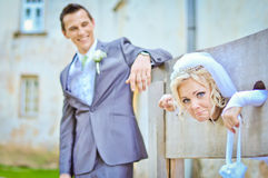 Bride and Groom. At their wedding day. Bride is locked in slaves clamps and groom is laughing. Background is blurred in bokeh. He has silver/black suit and she Stock Photos