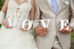 Bride and groom. Closeup shot of bride and groom hands holding the word Love Stock Images