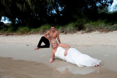 Bride and Groom 3. Bride and groom relax on the beach during a Trash the Dress Session royalty free stock images