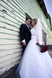 Bride and Groom. Outdoor portrait of a bride and groom by the side of a shingled building with peeling paint.  Groom is standing against the building, while the Royalty Free Stock Images