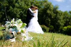 Bride and groom. Bunch of white roses and newly-weds on a green background Stock Images