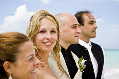 Bride and groom. With groomsmen and bridesmaid on the beach. Bride looking at camera Stock Images