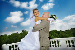 Bride and groom. Embracing against beautiful cloudy sky Royalty Free Stock Photography