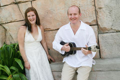 Bride and groom. Groom playing the guitar to his new bride - black and white image royalty free stock photography