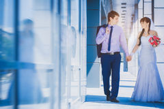 Bride and groom against a blue modern building Royalty Free Stock Photo