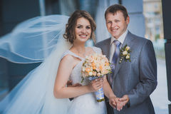 Bride and groom against a blue modern building Stock Image