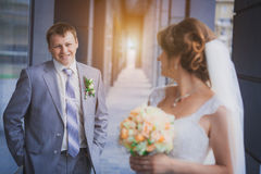 Bride and groom against a blue modern building Royalty Free Stock Image