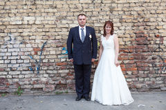 Bride and groom against brick wall Royalty Free Stock Photo