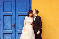 Bride and groom against yellow wall and blue door Stock Photos