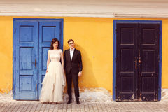Bride and groom against yellow wall and blue door Royalty Free Stock Image
