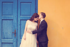 Bride and groom against yellow wall and blue door Royalty Free Stock Photo