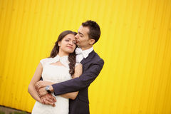 Bride and groom against a yellow wall Stock Photos