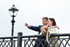 Bride and groom around the fence of the bridge Stock Images