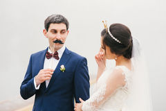Bride and groom attached to  face paper mustache ,  crown Royalty Free Stock Photo