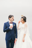 Bride and groom attached to  face paper mustache ,  crown Stock Photos