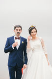 Bride and groom attached to  face paper mustache ,  crown Royalty Free Stock Images