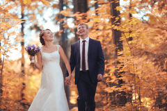 Bride and groom in autumn park Stock Images