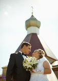 Bride and groom on background of Christian Church Stock Images