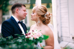 Bride and groom on the background of the garden fence.  Stock Photo