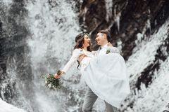 Bride and groom on the mountain waterfall royalty free stock image