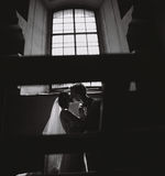 Bride and groom on the background of a window. Bride and groom posing on the background of a large window Stock Image