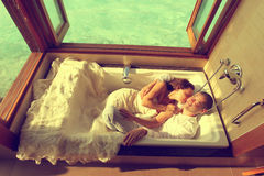 Bride and groom in bath tub in Maldives Stock Images
