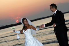 Bride and groom on the beach. Bride and groom walking on the beach Stock Photos
