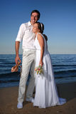 Bride and groom at the beach. Bride and groom posing at the beach after their wedding Royalty Free Stock Images