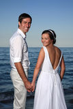 Bride and groom at the beach. Bride and groom posing at the beach after their wedding Stock Images