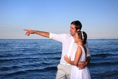 Bride and groom at the beach. Bride and groom posing at the beach after their wedding Stock Photography