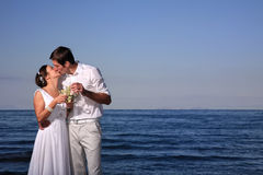 Bride and groom at the beach. Bride and groom posing at the beach after their wedding Royalty Free Stock Photo