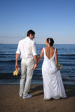 Bride and groom at the beach. Bride and groom posing at the beach after their wedding Stock Image