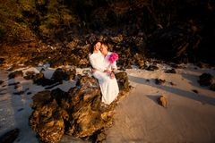 Bride and groom at beach against rocks at sunrise Stock Images
