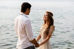 Newlyweds frolic in the water on the beach stock photo