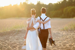 Bride and groom on a beach at sunset Royalty Free Stock Image