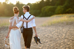 Bride and groom on a beach at sunset Royalty Free Stock Photography