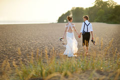 Bride and groom on a beach at sunset Stock Images