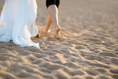 Bride and groom on a beach at sunset Stock Photos
