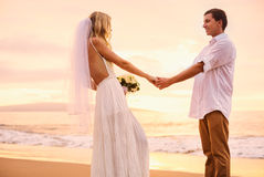 Bride and groom on beach at sunset Stock Photography