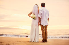 Bride and groom on beach at sunset Stock Images