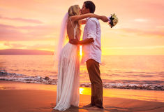 Bride and groom on beach at sunset Stock Photos