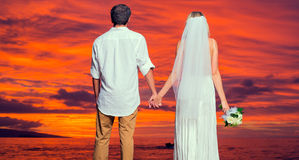 Bride and groom on beach at sunset Royalty Free Stock Photography