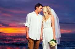 Bride and groom on beach at sunset Royalty Free Stock Photos