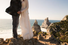 The bride and groom on the beautiful Cliff near the ocean Stock Photography