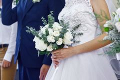 Bride and groom with a beautiful wedding bouquet at the ceremony.  Royalty Free Stock Image