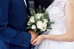 Bride and groom with a beautiful wedding bouquet at the ceremony Stock Photos