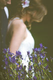 Bride and Groom Behind Irises. Wedding Couple in Background Behind Irises Stock Images